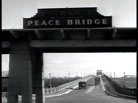 Peace Bridge entrance arch sign two cars moving BG Cars in line at toll bridge Canada customs official walking to car hand holding out paper officer...