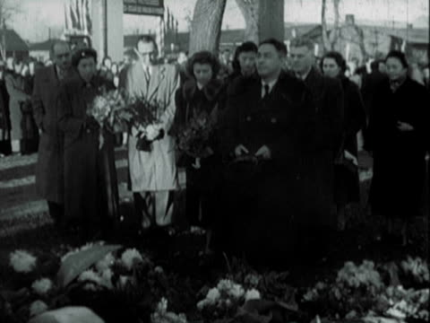 Peace congress delegates placing wreath leaving flowers at Auschwitz concentration camp in Poland / people bowing heads reverently writing in...