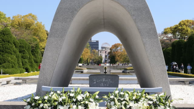 peace memorial park with peace flame and a-bomb dome in background, hiroshima, japan - 記念碑点の映像素材/bロール