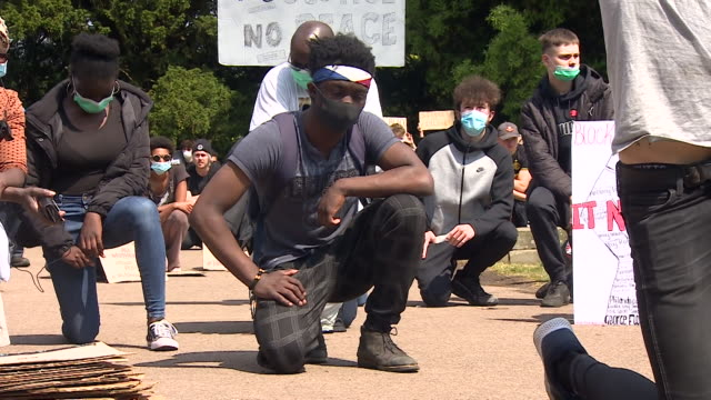 peaceful black lives matter protest in park in cheltenham with protesters in silence taking the knee - ひざまずく点の映像素材/bロール