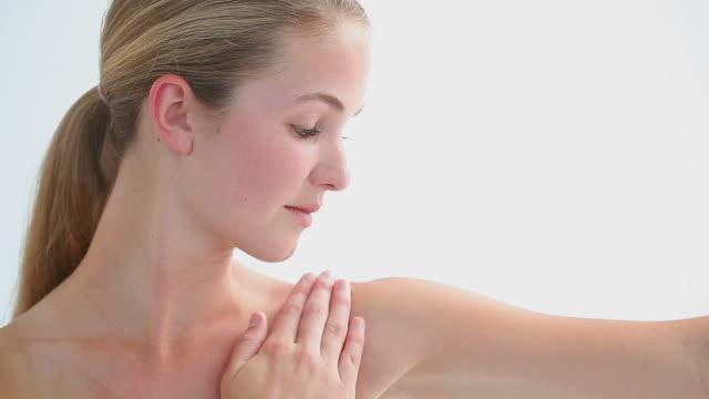 vídeos de stock, filmes e b-roll de peaceful blonde woman massaging her shoulder - cabelo preso