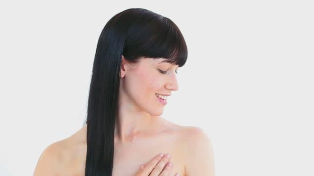 Peaceful brunette woman massaging her shoulder