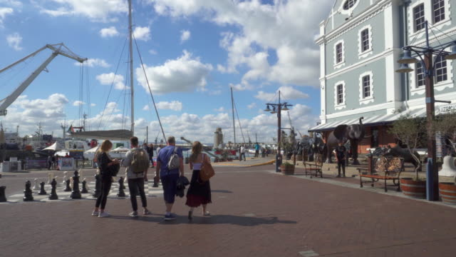 a peaceful pov following tourists walking on a sunny quayside in cape town on a sunny day near harbor with sailboats - cape town stock videos & royalty-free footage
