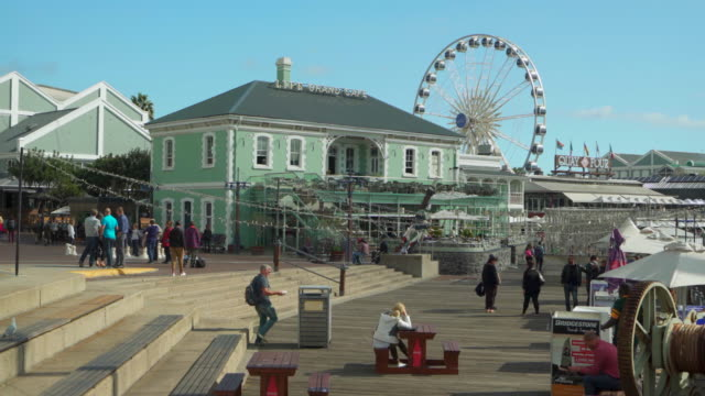 a peaceful lockdown of tourists moving about on cape town's sunny boardwalk by the harbor in front of a large ferris wheel - uferviertel stock-videos und b-roll-filmmaterial