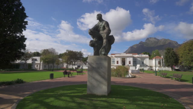 stockvideo's en b-roll-footage met a peaceful pan of a bronze statue in the middle of the rhodes memorial park under dark cliffs on a sunny day - cape town, south africa - memorial