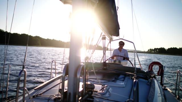 peaceful sunset on a lake. young man enjoying sailing - yacht stock videos & royalty-free footage