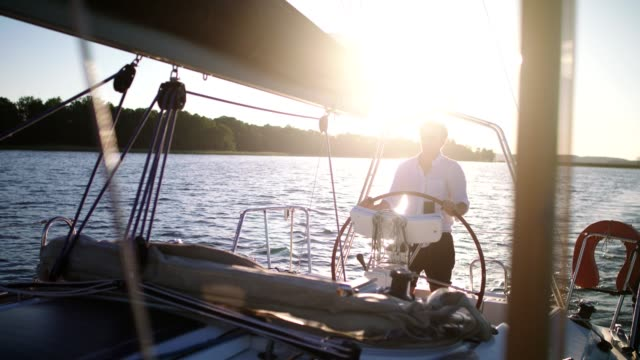 peaceful sunset on a lake. young man enjoying sailing - outdoor pursuit stock videos & royalty-free footage