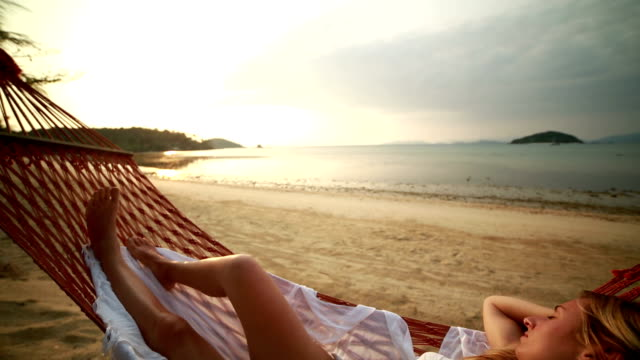 Peaceful woman relaxing on hammock-Tropical beach