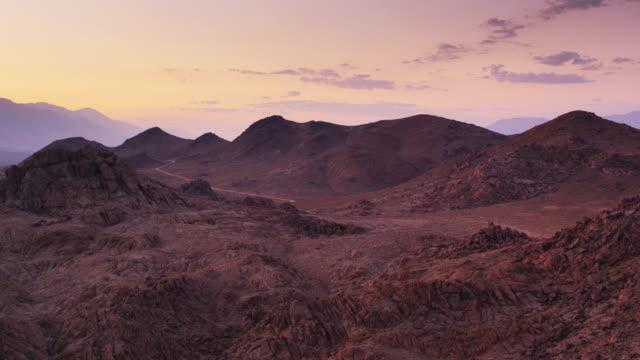 stockvideo's en b-roll-footage met perzik en violet zonsondergang over de alabama hills, californië - drone shot - californian sierra nevada