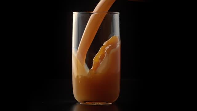 vídeos y material grabado en eventos de stock de melocotón / jugo de albaricoque que se vierte en el vaso - zumo de naranja