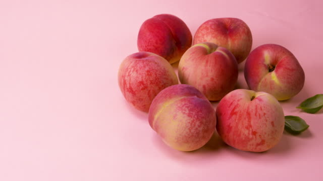 a peach rolling against pink backgrounds / south korea - fruit stock videos & royalty-free footage
