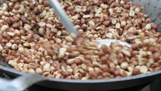 vídeos y material grabado en eventos de stock de asado de maní en la sartén - peanut food