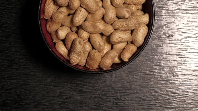 peanuts are in black cups. on black wood floor - nutshell stock videos and b-roll footage