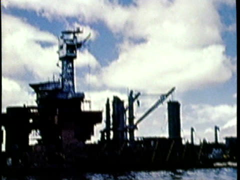 Pearl Harbor / No Audio / Images taken from a boat of Pearl Harbor after the attack in 1941 / Water level footage of rig in ocean / camera bobs up...
