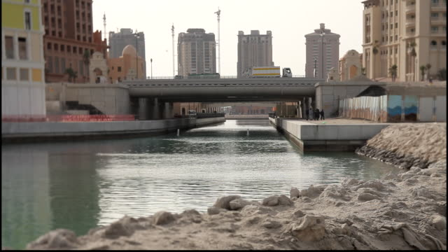 pearl island qatar view of a road bridge over a seawater canal and tower blocks on the artificial pearl island - bridge built structure stock videos & royalty-free footage