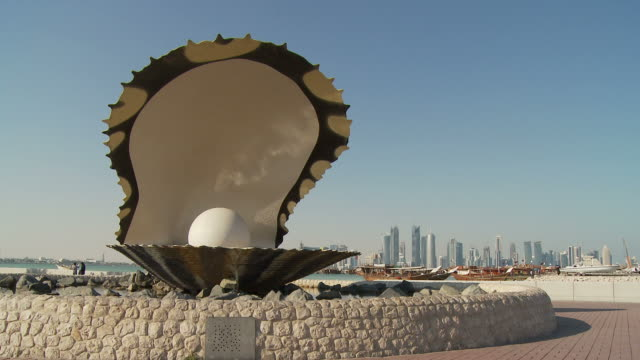 ws pearl monument, city skyline seen across doha bay in distance / doha, qatar - doha stock videos & royalty-free footage