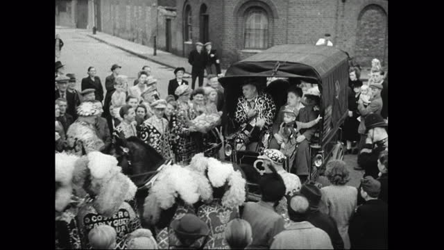 pearly king and queen drive cart through crowd at harvest festival; 1949 - english culture stock videos & royalty-free footage