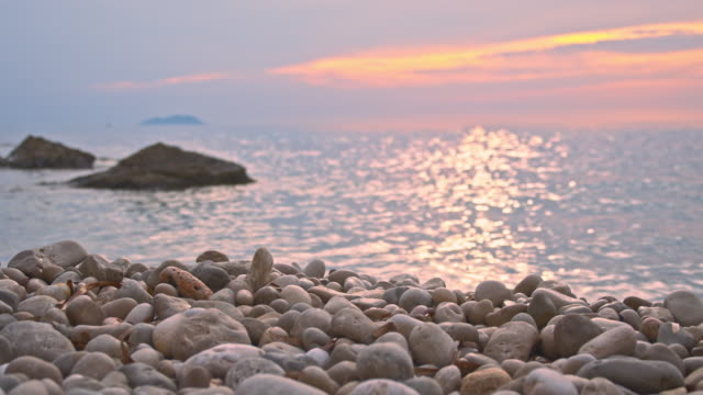 slo mo pebble beach bei sonnenuntergang - schöne natur stock-videos und b-roll-filmmaterial