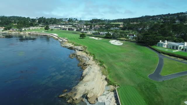 pebble beach shoreline golf course - drone - lift from green over ocean - golfplatz stock-videos und b-roll-filmmaterial