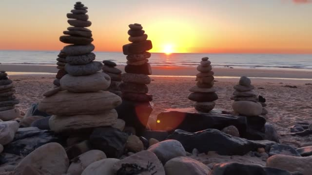 stockvideo's en b-roll-footage met pebble sculptures have formed on whitley bay beach on the north east coast while people are taking their daily lockdown exercise they have kept... - whitley bay