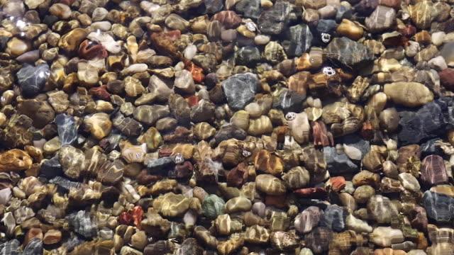 vídeos de stock, filmes e b-roll de pedras de pedra na água - pedra solta