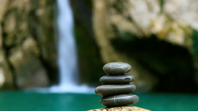 pebble stones over waterfall - stack rock stock videos and b-roll footage