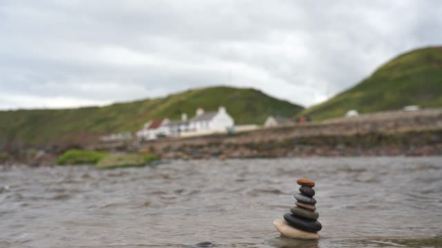 vidéos et rushes de pebble tower by the seaside at saltburn by the sea in uk, stack of zen stones in the river  with blurry pub and mountain background, stack rock pyramid on the beach symbolizing, stability, harmony, balance with shallow depth of field. - sans mise au point and équilibre