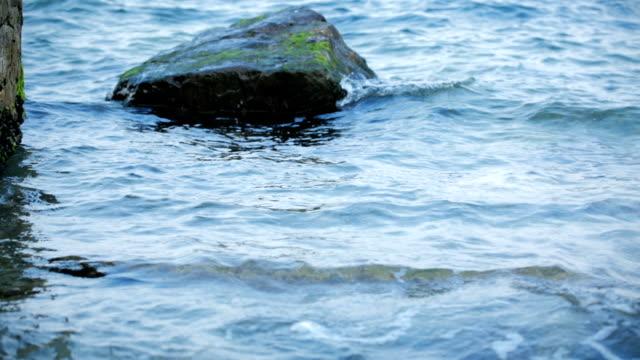 Pebbles on the wavy beach. Camera tilt up