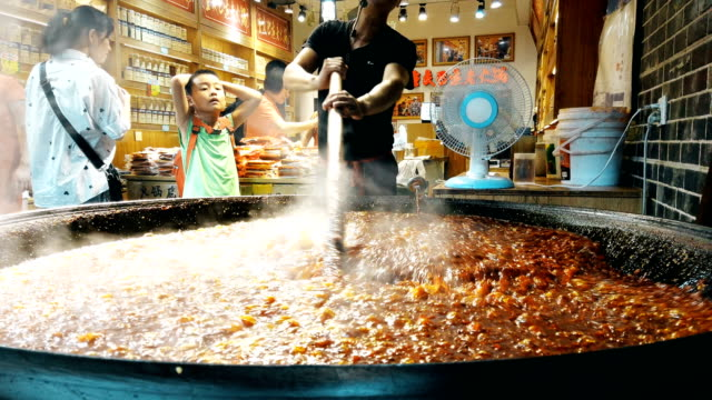 peddler cooking hot pot seasoning in ciqikou ancient town,chongqing,china. - boiler stock videos & royalty-free footage