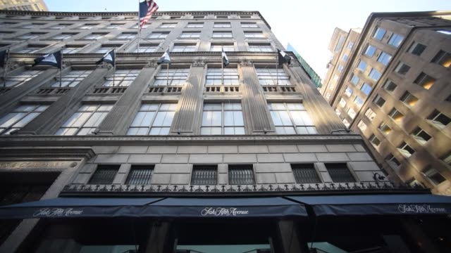 Pedestrains pass the Saks Fifth Avenue Flagship store in New York New York United States on September 25 Wide shots and close ups of Saks Company...