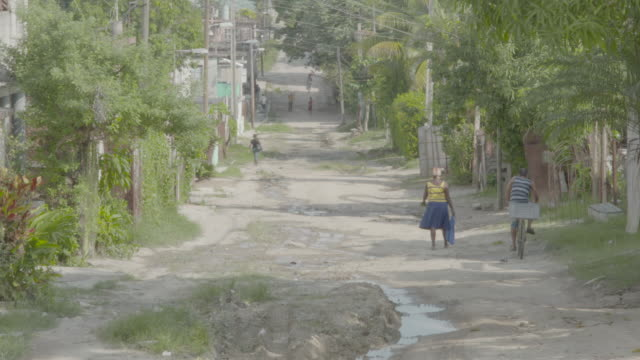 pedestrian and bicyclist travel down dirt road in havana, cuba - ムラがある点の映像素材/bロール