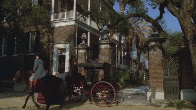 MS, REENACTMENT Pedestrian and horse-drawn carriage in front of large brick mansion, 19th century style