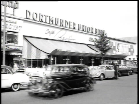 stockvideo's en b-roll-footage met pedestrian and vehicular traffic on street in front of dortmunder union building / berlin, germany - 1955