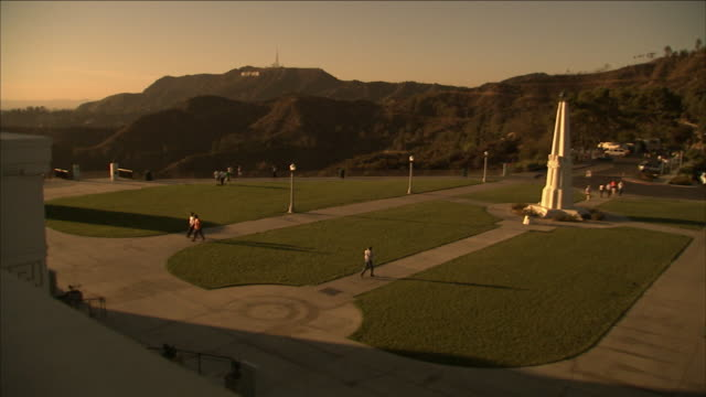 a pedestrian approaches the astronomer's monument at the griffith observatory in los angeles. - griffith observatory stock videos & royalty-free footage