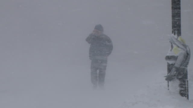 A pedestrian braves near whiteout conditions and powerful winds during a New England blizzard