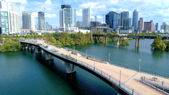 vídeos de stock e filmes b-roll de pedestrian bridge fly over town lake and austin texas iconic skyline sunny afternoon daytime - town