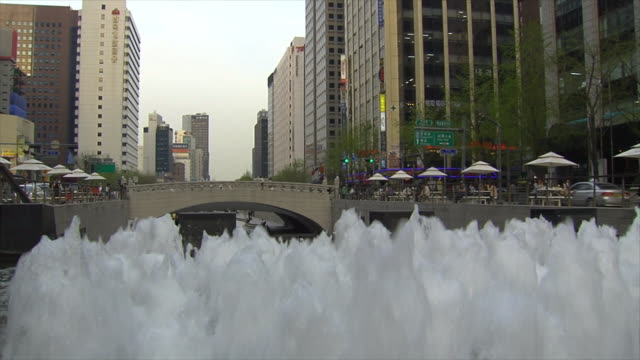 pedestrian bridge over cheonggyecheon stream riverwalk, umbrella tables lining upper banks, city buildings bg, top of fountain w/ multiple white... - isle of man stock videos & royalty-free footage