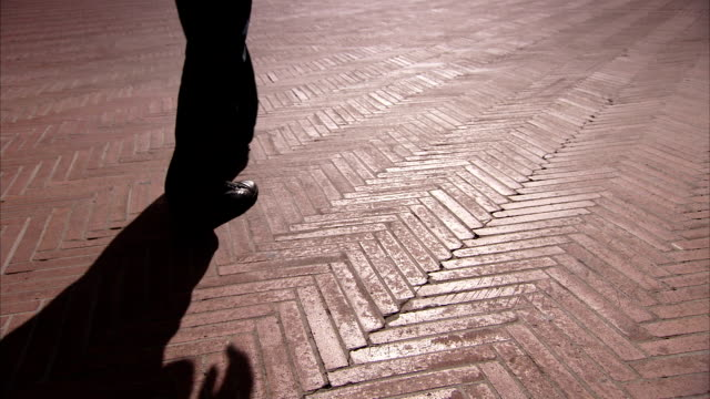 a pedestrian casts a shadow along the bricked walkway of the palazzo communale in montepulciano. available in hd. - montepulciano stock videos & royalty-free footage