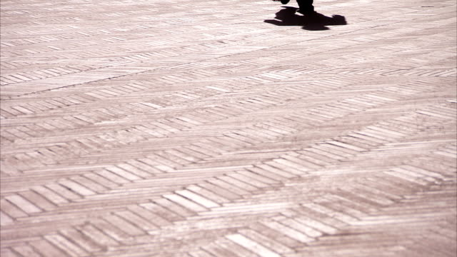 a pedestrian casts a shadow on the tiled walkway of the palazzo communale in montepulciano. available in hd. - montepulciano stock videos & royalty-free footage