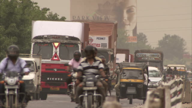 a pedestrian crosses a busy highway in india. available in hd - billboard stock videos & royalty-free footage