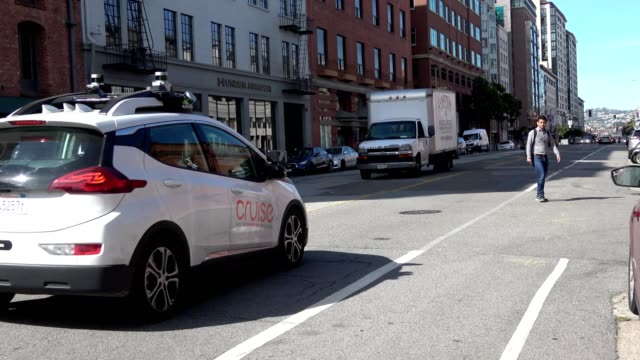 pedestrian crosses a road in the south of market neighborhood of san francisco, california as a general motors cruise self-driving car enters the... - cruise collection stock videos & royalty-free footage