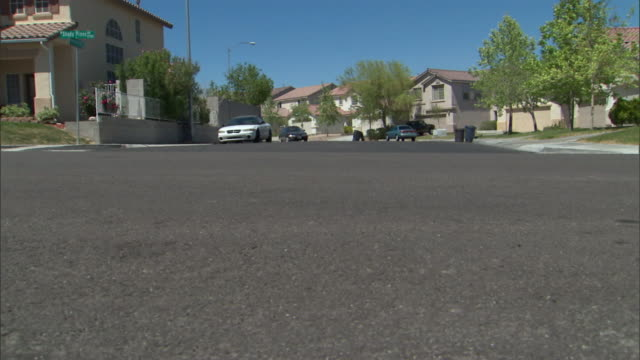 a pedestrian crosses a street in a residential area. - las vegas crosses stock-videos und b-roll-filmmaterial