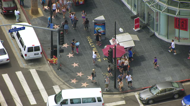 ws zo aerial pov pedestrian crossing intersection and walking on hollywood walk of fame / los angeles, california, united states - ウォークオブフェーム点の映像素材/bロール