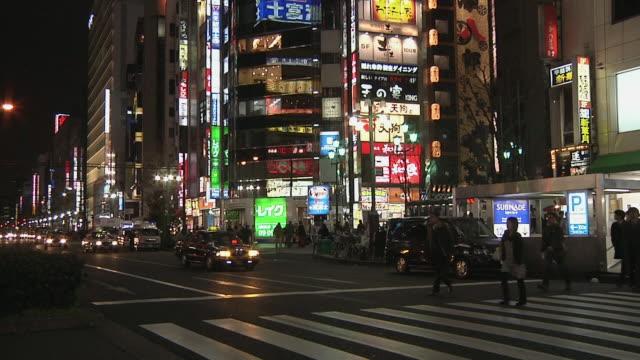 ws tu pedestrian crossing on shinjuku street at night / tokyo, kanto, japan - japan stock videos & royalty-free footage