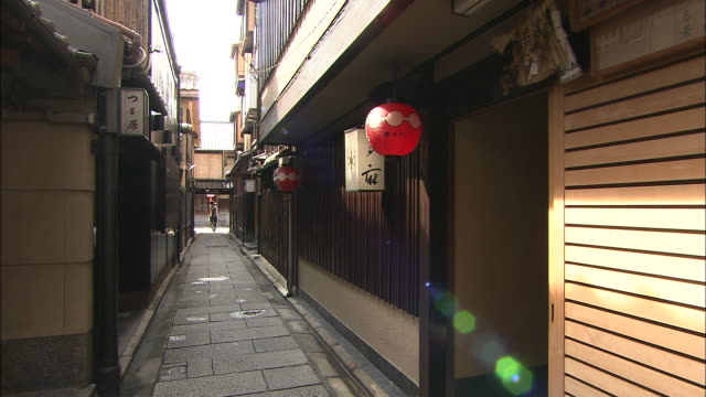 A pedestrian enters an alleyway in the Gion district of Kyoto.