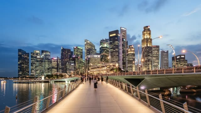 pedestrian footbridge leading to the singapore financial district, busy with people, at dusk - population explosion stock videos & royalty-free footage
