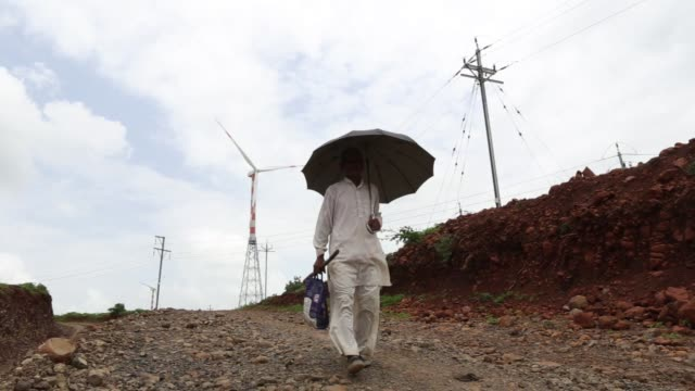 a pedestrian holding an umbrella walks near a wind turbine manufactured by suzlon energy ltd operating beyond electricity pylons at the ostro energy... - madhya pradesh stock videos and b-roll footage