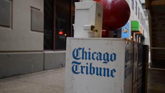 pedestrian passes a chicago tribune honor box in chicago, illinois, us, a pedestrian passes a chicago tribune honor box in chicago, illinois, us, low... - トリビューンタワー点の映像素材/bロール