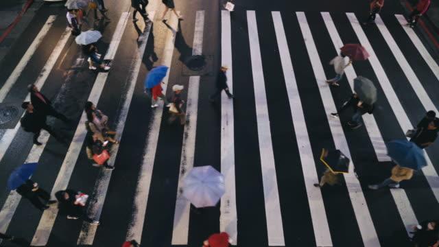 vídeos de stock, filmes e b-roll de taipei, taiwan - pessoas pedestres atravessaram uma estrada em dia de chuva - cruzando