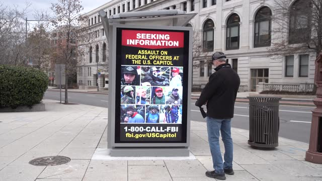 pedestrian photographs the fbi's poster on january 17, 2021 in washington, dc. the poster identifies those wanted for questioning in the insurrection... - 就任式点の映像素材/bロール